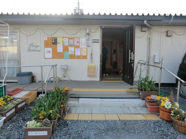 花で彩が添えられている仮設住宅団地集会所の前