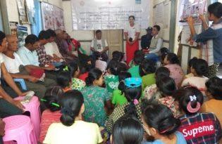 村人を集めて保健衛生・健康意識の向上活動の説明を行う_