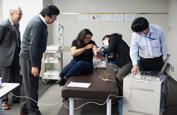 東都大学で、筋電図を測定する機器を取り付けている様子。